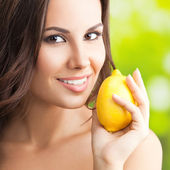 Smiling woman with lemon, outdoors — Stock Photo
