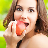 Woman eating red apple, outdoor — Stock Photo