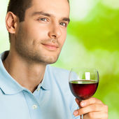 Handsome man with glass of redwine, outdoor — Stock Photo