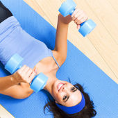 Woman exercising with dumbbells, indoor — Stock Photo