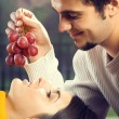 Portrait of young couple eating grapes, outdoor — Stock Photo #63511467