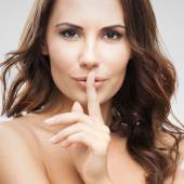 Woman with finger on lips, on grey — Stock Photo
