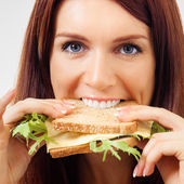 Happy young woman eating sandwich with cheese — Stock Photo