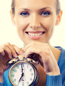 Portrait of young smiling woman with alarmclock — Stock Photo