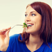 Portrait of young beautiful woman eating broccoli — Stock Photo