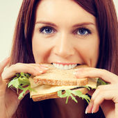 Portrait of young beautiful woman eating sandwich with cheese — Stock Photo