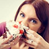 Portrait of young hungry woman eating pie — Stock Photo