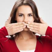 Young woman covering mouth, on grey — Stock Photo