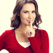 Young woman keeping finger on her lips — Stock Photo
