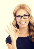 Young businesswoman in glasses with okay gesture — Stock Photo