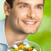 Young happy man with salad, outdoors — Stok fotoğraf