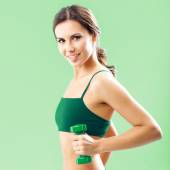 Woman in fitness wear with dumbbell, on green — Stock Photo