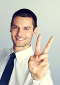 Young businessman showing two fingers — Stock Photo
