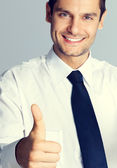 Young smiling businessman with thumbs up gesture — Stock Photo