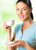Young happy smiling woman drinking coffee — Stock Photo