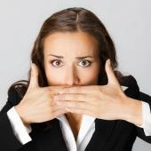Businesswoman covering with hands her mouth, on grey — Stock Photo