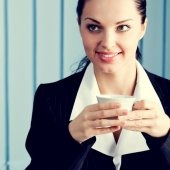 Happy businesswoman with laptop drinking coffee — Stock Photo