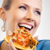 Woman eating pizza, on grey — Stock Photo