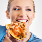 Young woman eating pizza, on grey — Stock Photo