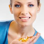 Woman with assorted pills and capsules — Stock Photo