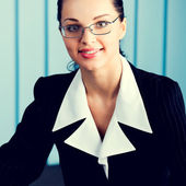 Happy smiling young businesswoman at office — Stock Photo