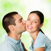 Portrait of young happy couple kisssing, outdoors — Stock Photo