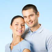 Young happy smiling amorous attractive couple, on blue sky  — Stock Photo