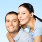Young smiling amorous attractive couple, over blue sky  — Stock Photo