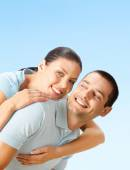 Happy smiling young couple, over blue  — Stock Photo