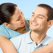 Young cheerful smiling amorous couple, on blue sky  — Stock Photo