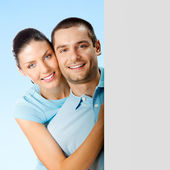 Smiling couple, over blue, showing blank signboard — Stock Photo