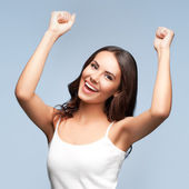 Happy gesturing young woman, over grey — Stock Photo