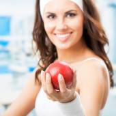 Happy woman giving red apple, at fitness center — Stock Photo