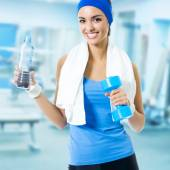 Woman in blue sportswear with bottle of water and dumbbell, at f — Stock Photo
