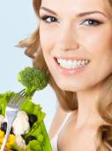 Woman eating vegetarian salad with broccoli, on blue — Stock Photo