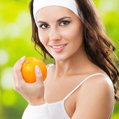 Young happy smiling woman with orange, outdoors — Stockfoto