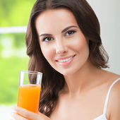 Happy smiling young woman drinking orange juice — Stock Photo