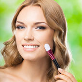 Smiling blond woman with make up brush, outdoor — Stock Photo