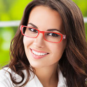 Portrait of young happy brunette businesswoman in glasses — Stock Photo