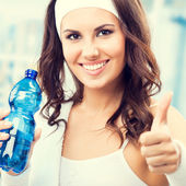 Happy woman with bottle of water, at fitness club — Stock Photo