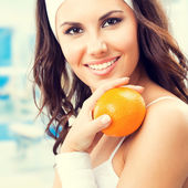 Woman with orange, at gym — Stock Photo