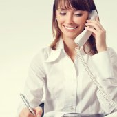Businesswoman with phone writing — Stock Photo