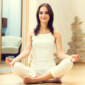 Brunette woman doing yoga exercises, indoors — Stock Photo