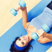 Brunette woman exercising with dumbbells, indoor — Stock Photo