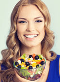 Lovely woman with vegetarian salad, over blue — Stock Photo