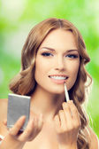 Happy smiling lovely woman with make up brush and mirror, outdoo — Stock Photo