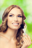 Smiling blond young lovely woman with make up brush, outdoor — Stock Photo