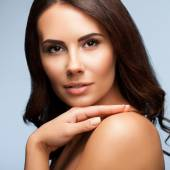 Portrait of beautiful young woman with naked shoulders, on grey — Stock Photo