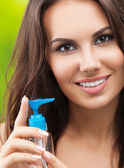 Young woman with body lotion, outdoor — Stock Photo