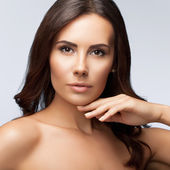 Beautiful young woman with naked shoulders, on bright grey — Stock Photo